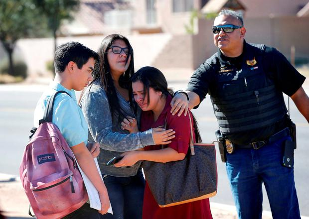 Students embrace after leaving campus, Friday, Feb. 12, 2016, in Glendale, Ariz. after two teens were shot Friday at Independence High School in the Phoenix suburb.(AP Photo/Matt York)