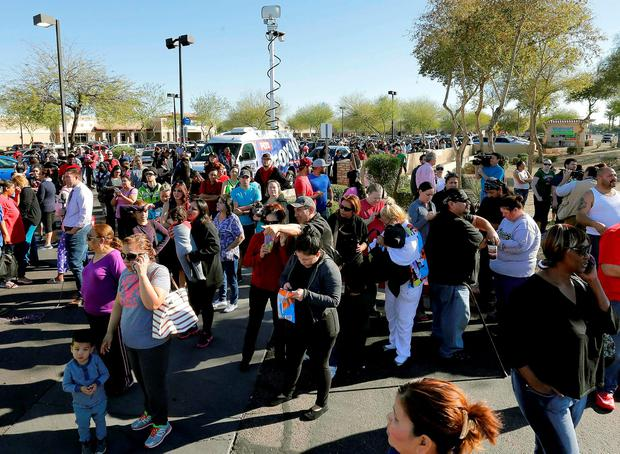 Parents wait to reunite with their children, Friday, Feb. 12, 2016, in Glendale, Ariz., after two students were shot and killed at Independence High School in the Phoenix suburb. (AP Photo/Matt York)