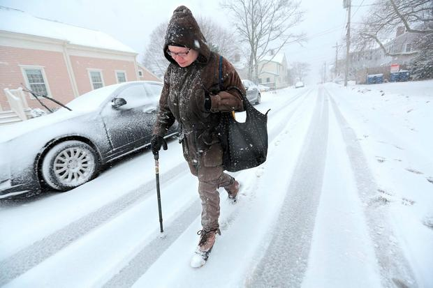 Anne Correia walks in a snowstorm to visit her mother at a nursing home . (Peter Pereira/Standard Times via AP)