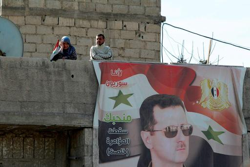 Residents stand near a picture of Syria's president Bashar al-Assad in Wafideen Camp, which is controlled by Syrian government forces, in Damascus suburbs, Syria REUTERS/Omar Sanadiki
