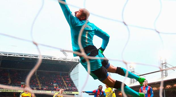Heurelho Gomes of Watford dives in vain as Emmanuel Adebayor of Crystal Palace scores. Photo: Getty