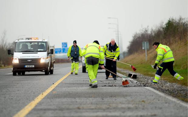 Gardai helping motorway maintenance workers clear the debris from crash Picture: Caroline Quinn