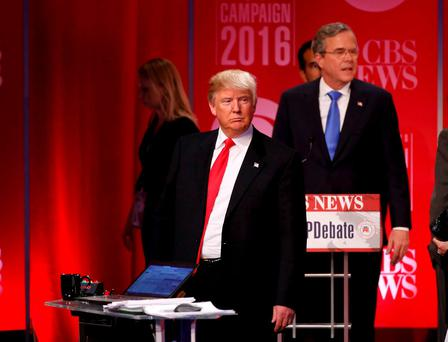 Republican U.S. presidential candidate former Governor Jeb Bush (rear) walks past rival candidate businessman Donald Trump as he stands at the front of the stage at the conclusion of the Republican U.S. presidential candidates debate sponsored by CBS News and the Republican National Committee in Greenville, South Carolina February 13, 2016. REUTERS/Jonathan Ernst