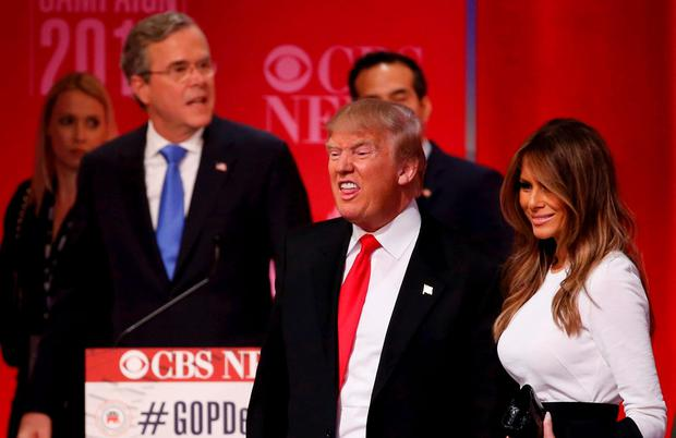 Republican U.S. presidential candidate former Governor Jeb Bush (rear) walks past rival candidate businessman Donald Trump and his wife Melania (R) as they stand at the front of the stage at the conclusion of the Republican U.S. presidential candidates debate sponsored by CBS News and the Republican National Committee in Greenville, South Carolina February 13, 2016. REUTERS/Jonathan Ernst