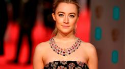 Saoirse Ronan poses on arrival for the BAFTA British Academy Film Awards at the Royal Opera House in London