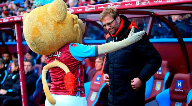 Liverpool manager Jurgen Klopp is welcomed by Aston Villa mascot Herclues the Lion