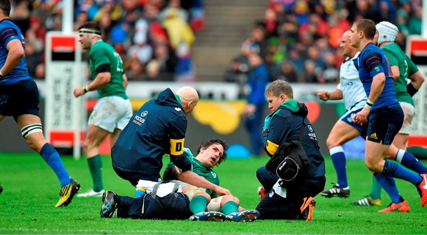 Mike McCarthy, Ireland, is attended to by team doctor Dr. Jim McShane and team physio James Allen before being stretchered off. Photo: Sportsfile