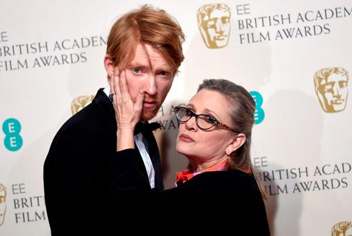 Actors Carrie Fisher and Domhnall Gleeson pose after presenting the award for Best film not in the English language at the British Academy of Film and Television Arts (BAFTA) Awards
