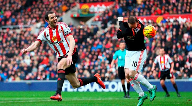 Wayne Rooney ducks for cover as John O'Shea gets in a header at the Stadium of Light. Photo: Getty