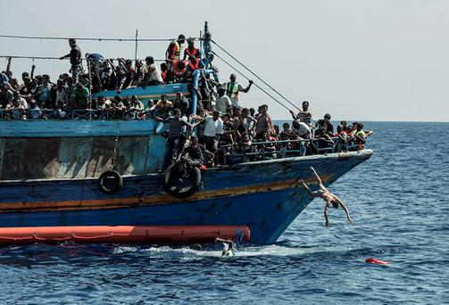Migrants being smuggled into Europe abandon ship to swim towards their rescuers. Photo: Christophe Stramba/MSF