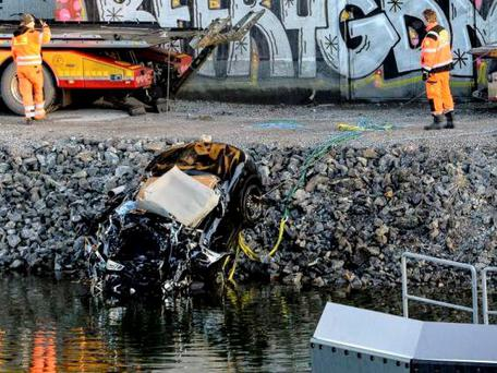 A badly damaged car is towed up from the canal under the E4 highway bridge in Sodertalje, Sweden,