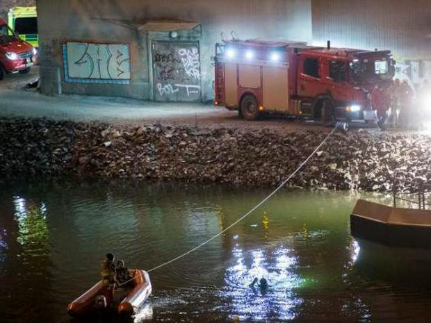 Divers and rescue service personnel search for the victims of the deadly car crash in the canal under the E4 highway bridge