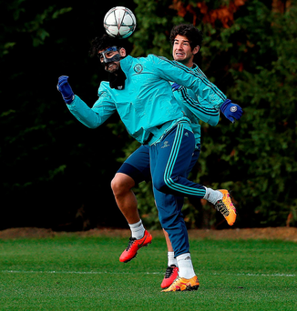 Diego Costa - wearing a protective mask - challenges Alexandre Pato during Chelsea training yesterday. Photo: Adrian Dennis/AFP/Getty Images