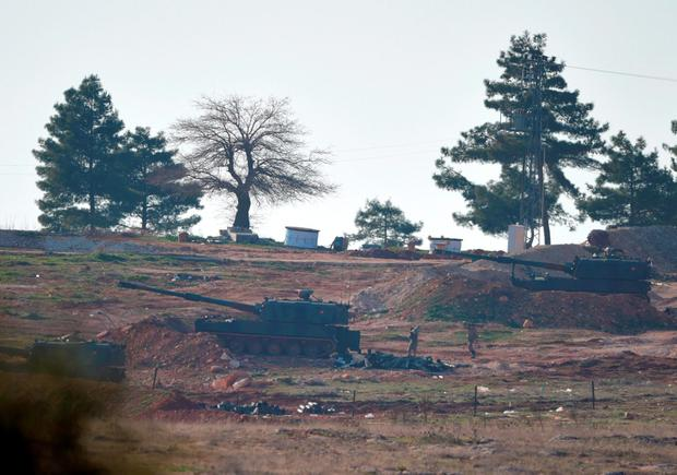 Soldiers carry ammunition as Turkish artillery fire from the border near Kilis toward northern Syria, in Kilis. Photo: AP