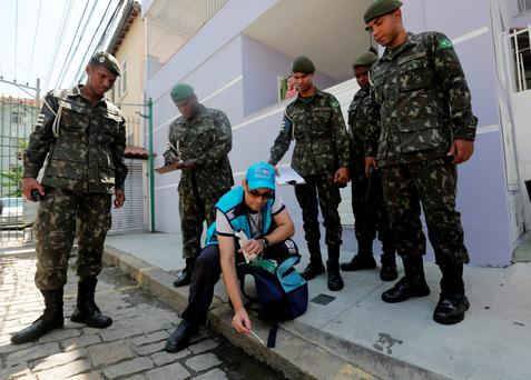 Surrounded by soldiers, a government health agent uses larvicide to kill Aedes aegypti mosquitos that spreads the Zika virus in the Tijuca neighborhood of Rio de Janeiro. Photo: AP
