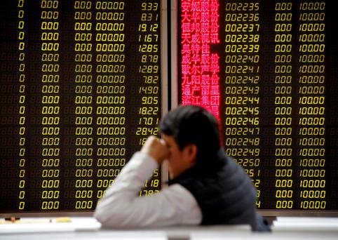 An investor sits in front of an electronic stock information board displaying zero numbers on the latests stock prices before the opening of the first trading day after the week-long Lunar New Year holiday at a brokerage house in Beijing. Photo: Reuters