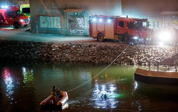 Divers and rescue service personnel search for the victims of the deadly car crash in the canal under the E4 highway bridge in Sodertalje, Sweden