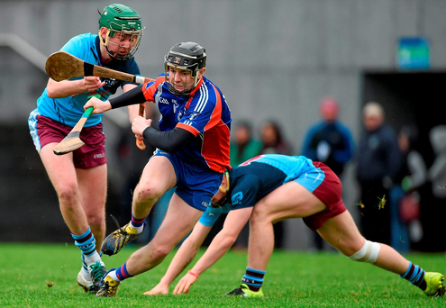 Conor Gardiner, left, supported by team-mate Jarlath Mannion, Galway Mayo Institute of Technology, breaks his hurl across the shoulder of Alan Flynn, Mary Immaculate College, Limerick. Photo: Diarmuid Greene / Sportsfile
