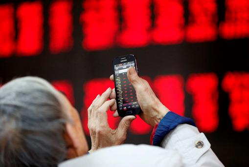 An investor checks stock information on his mobile phone in front of an electronic board showing stock information at a brokerage house in Beijing. Photo: Reuters
