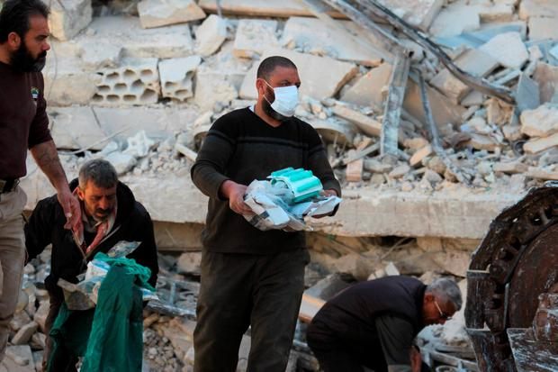 People carry medical supplies found under the rubble of a destroyed Medecins Sans Frontieres (MSF) supported hospital hit by missiles in Marat Numan, Idlib province, Syria. Photo: Reuters