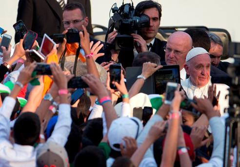 Young people photograph Pope Francis as he walks to greet them following a meeting with Mexican youth at Jose Maria Morelos y Pavon Stadium in Morelia, Mexico. (AP Photo/Rebecca Blackwell)