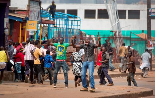 Some angry supporters of opposition leader Kizza Besigye flee from military police firing warning shots while others stand their ground, near to his party headquarters, in Kampala, Uganda. (AP Photo/Ben Curtis)