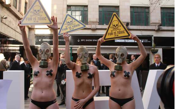 Animal rights protesters wearing gas masks and body paint crash London Fashion Week holding warning signs that read 'Fur is toxic'. Photo: Press Association.