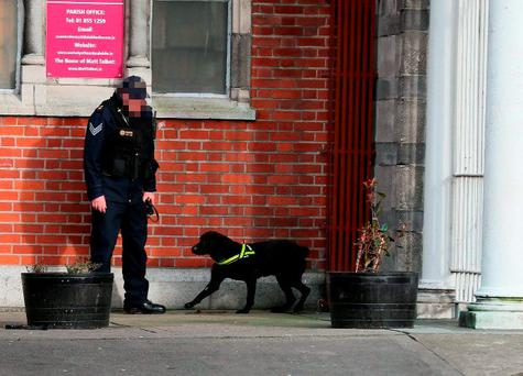 Garda sniffer dogs patrol the area around Our of Lourdes Church in Dublin before the funeral of Eddie Hutch senior.