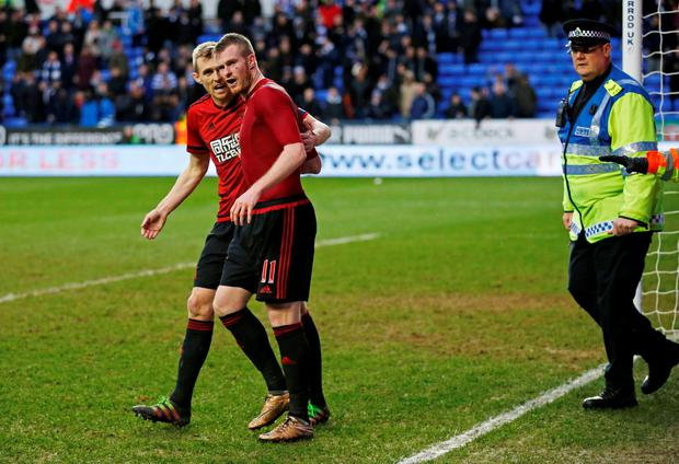 West Brom's Chris Brunt reacts after a coin is thrown at him from the crowd as Darren Fletcher looks on