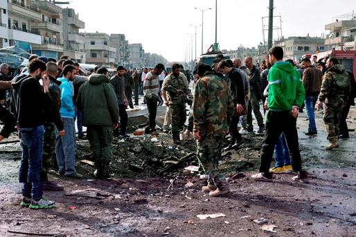 Syrian onlookers and security forces inspect a crater at the site of a double car bomb attack on February 21, 2016 in the Al-Zahraa neighborhood of the central Syrian city of Homs
