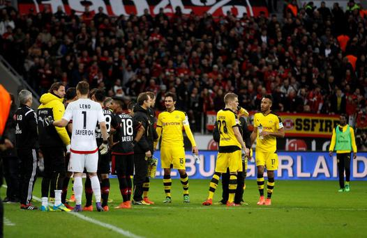 Borussia Dortmund and Bayer Leverkusen players leave the field after an interruption during the match