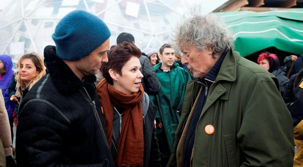 Handout photo issued by Help Refugees of Jude Law (left) and Sir Tom Stoppard talking to an unnamed woman after a one off Letters Live performance in association with Good Chance at the refugee camp in Calais, France.: Help Refugees/PA Wire