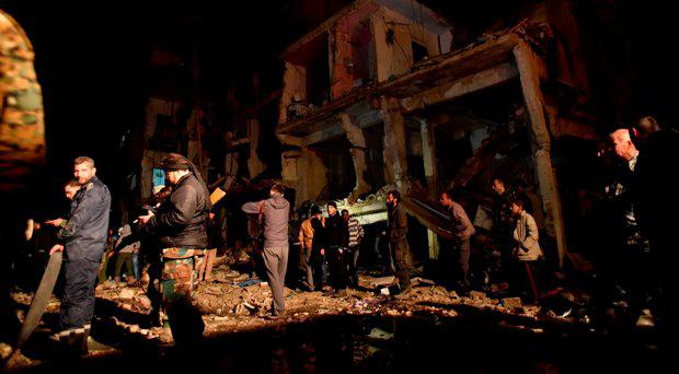 People gather in the aftermath of a multiple explosive attack in the Sayyida Zeinab area, 10 km south of Damascus, Syria, Sunday, Feb. 21, 2016