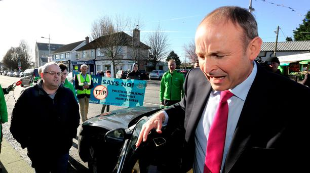 Micheál Martin is met by anti-austerity protesters as he prepares to canvass with FF Councillor Catherine Ardagh in Crumlin. Photo: Gerry Mooney