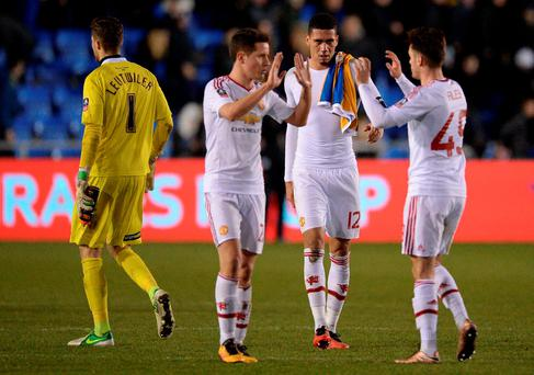 Manchester United's English defender Chris Smalling (2R) celebrates with teammates following the English FA Cup fifth round football match between Shrewsbury Town and Manchester United