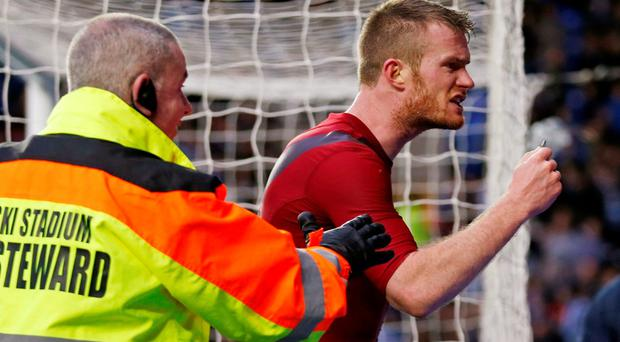 Chris Brunt reacts after having a coin thrown at him. Photo: Action Images via Reuters / Peter Cziborra