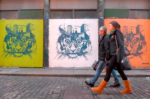 Pedestrians walk past graffiti in Dublin. Photo: Reuters