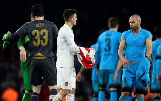Arsenal's Mesut Ozil swaps shirts with Barcelona's Javier Mascherano after the game