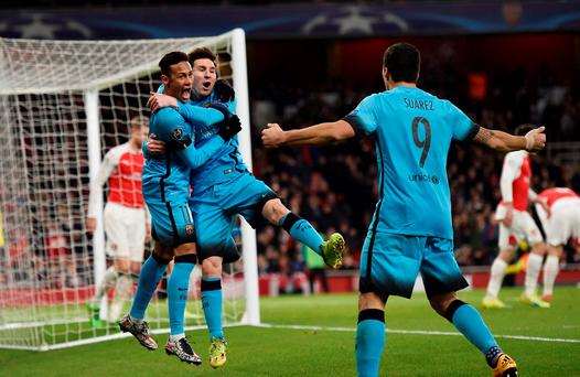 Lionel Messi celebrates with Neymar and Luis Suarez after scoring the first goal against Arsenal last February