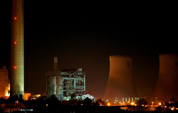 Part of a collapsed building is illuminated by the emergency services as they work at the decommissioned Didcot A power station in central England