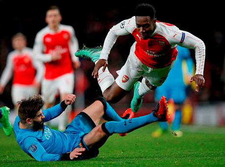 Barcelona's defender Gerard Pique (L) challenges Arsenal's English striker Danny Welbeck during the UEFA Champions League clash