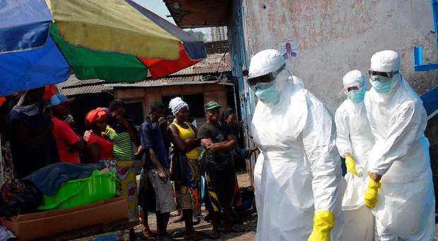 Red Cross workers in protective suits remove the body of an Ebola victim in Monrovia last year