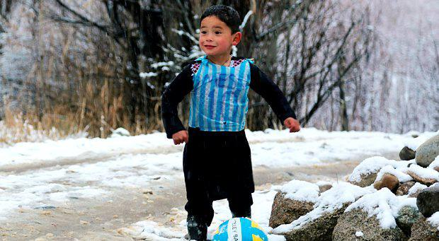 In this photograph taken on January 29, 2016, Afghan boy and Lionel Messi fan Murtaza Ahmadi, 5, wears a plastic bag jersey as he plays football in Jaghori district of Ghazni province