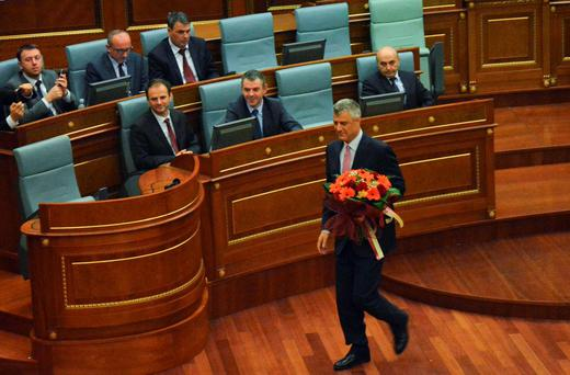 Kosovo Foreign Minister Hashim Thaci walk with flowers after being elected as the country's new president in a tense session as opposition activists released tear gas in the chamber and threw petrol bombs outside the parliament building in Pristina, Kosovo February 26, 2016. REUTERS/Agron Beqiri