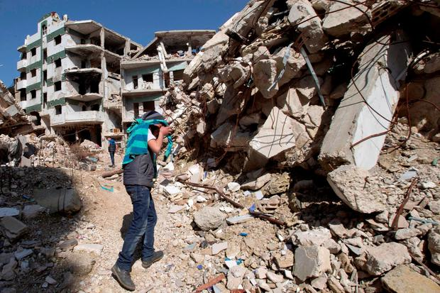 A Syrian covers his face as he walks with a friend between destroyed buildings in the old city of Homs, Syria. Photo: AP