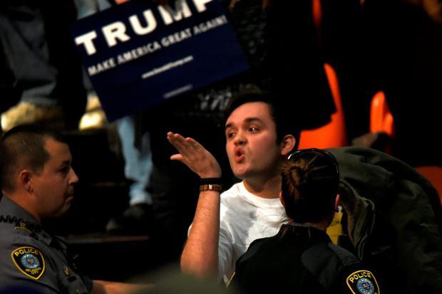 A protester blows a kiss to Republican U.S. presidential candidate Donald Trump as he is escorted out of a rally in Oklahoma City, Oklahoma February 26, 2016. REUTERS/Nick Oxford