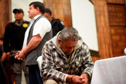 Heriberto Valdez Asij (R), a civilian who was attached to the Army, and former army officer Steelmer Francisco Reyes Giron (background) remain at a courtroom to listen to their sentence in Guatemala City