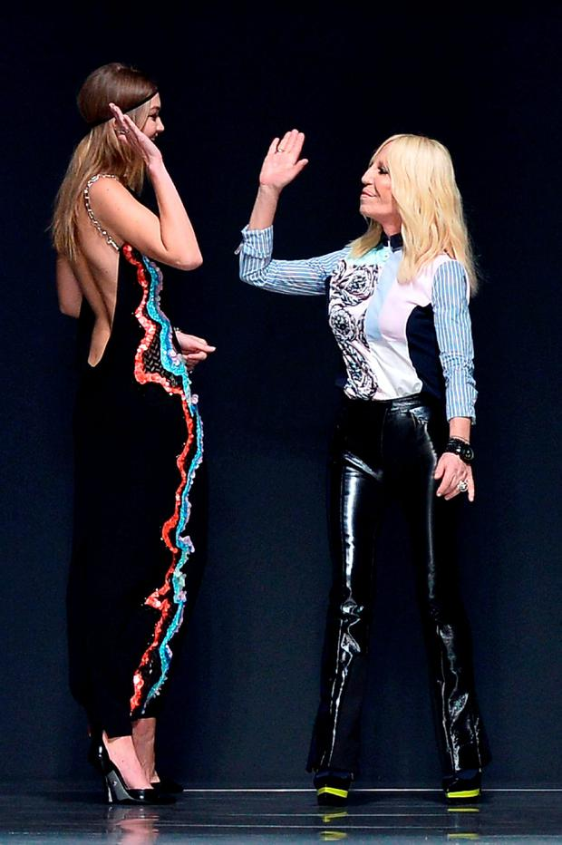 Model Gigi Hadid (L) and designer Donatella Versace shake hands at the end of the show for fashion house Versace as part of the Women Autumn / Winter 2016 Milan Fashion Week