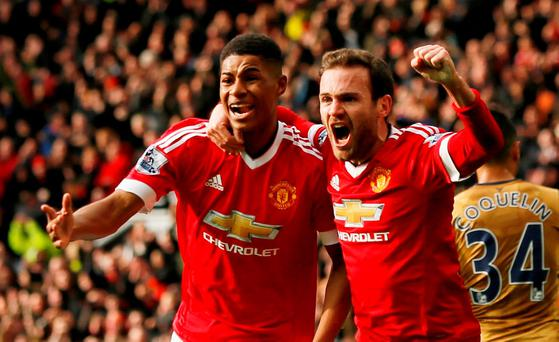 Manchester United's Marcus Rashford celebrates scoring their first goal with Juan Mata