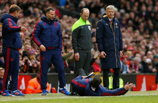 Manchester United manager Louis van Gaal lies on the side of the pitch to demonstrate a foul to the fourth official Mike Dean as Arsenal manager Arsene Wenger looks on